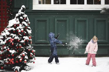 Siblings having a snowball fight at Chrismas time - EYAF00739