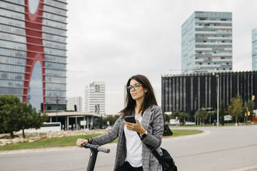 Young businesswoman using smartphone standing on e-scooter in the city - JRFF03905