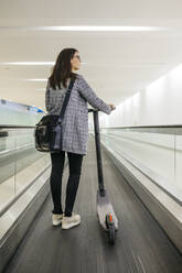 Businesswoman with her electric scooter on moving walkway - JRFF03914