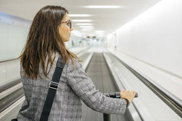 Businesswoman with her electric scooter on moving walkway - JRFF03917