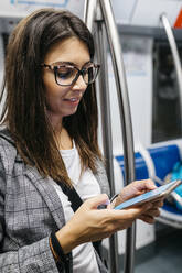 Brunette woman in the subway using the phone while traveling to work - JRFF03923
