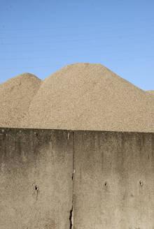 Germany, Berlin, Heap of sand behind wall - JMF00464