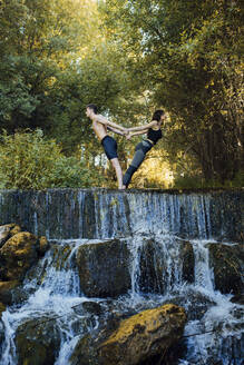 Couple practicing acro yoga together on a waterfall - MIMFF00007