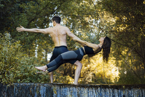 Couple practicing acro yoga together on a waterfall - MIMFF00013