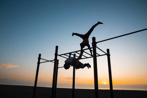 Two young men practicing calisthenics at an outdoor gym at sunrise - MIMFF00019