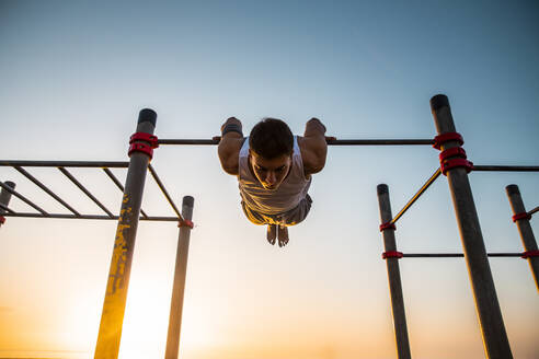 Young man practicing calisthenics at an outdoor gym at sunrise - MIMFF00022