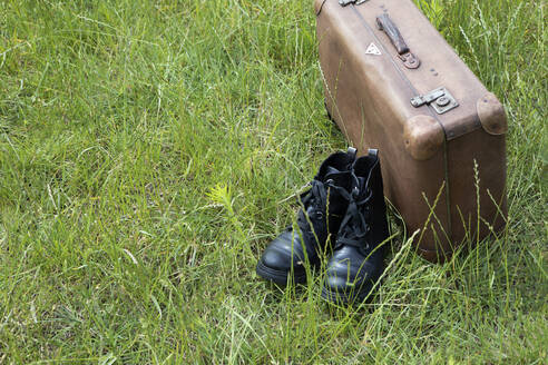Old brown leather suitcase and pair of black boots on a meadow - PSTF00487