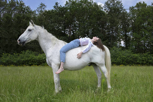 Young woman lying on back of a horse - PSTF00514