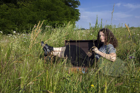 Portrait of young woman sitting in suitcase on a meadow - PSTF00541
