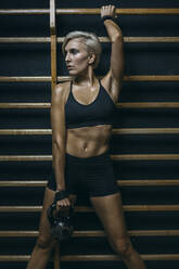 Blond sportswoman with dumbbell at wall bars - MADF01437