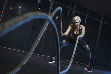 Blond sportswoman having workout with ropes - MADF01440