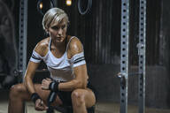 Portrait of blond sportswoman wearing white t-shirt and sweatband in gym - MADF01446