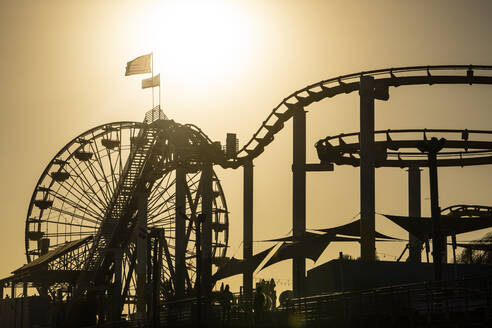 USA, California, Santa Monica, Silhouettes of Ferris wheel and rollercoaster of Santa Monica Pier at sunset - SEEF00068