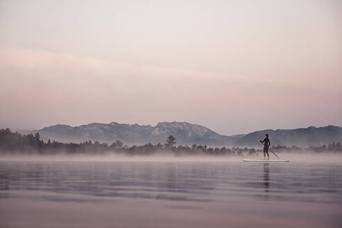 Woman stand up paddling on lake Kirchsee at morning mist, Bad Toelz, Bavaria, Germany - WFF00195