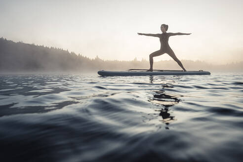 Woman practicing paddle board yoga on lake Kirchsee in the morning, Bad Toelz, Bavaria, Germany - WFF00198