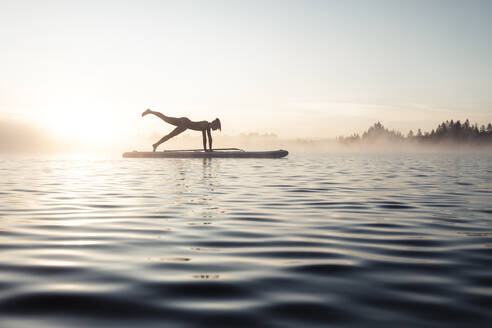 Woman practicing paddle board yoga on lake Kirchsee in the morning, Bad Toelz, Bavaria, Germany - WFF00201