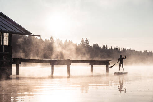 Silhouette of a woman stand up paddling on lake Kirchsee at morning mist, Bad Toelz, Bavaria, Germany - WFF00207