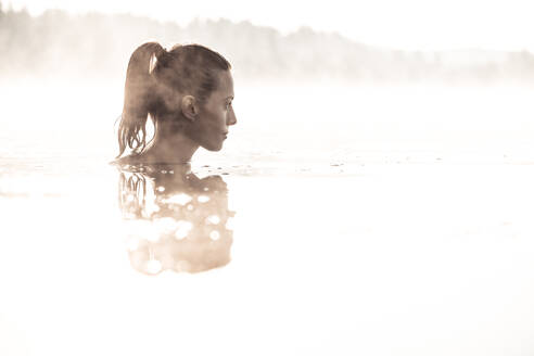 Woman bathing in a lake at morning mist - WFF00213