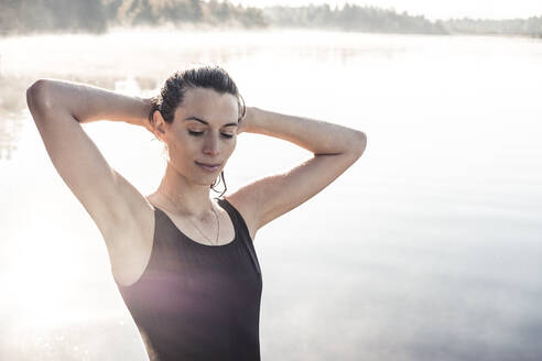 Woman wearing black swimsuit at a lake at morning mist - WFF00216