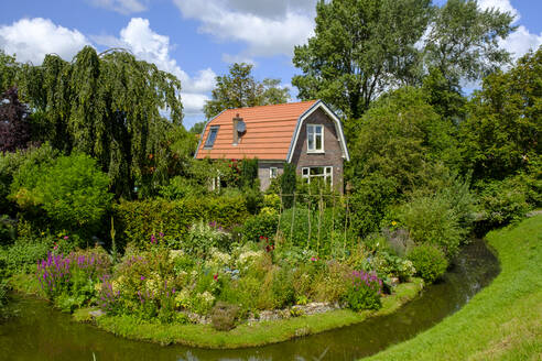 Netherlands, North Holland, Hoorn, Lake Ijssel ditch stretching in front of blooming garden of rustic house - LBF02831