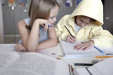 Brother and sister sitting at table at home doing homework together - EYAF00741