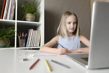 Girl sitting at table at home doing homework and using laptop - EYAF00747