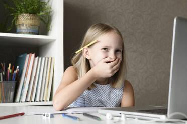 Laughing girl sitting at table at home using laptop - EYAF00750