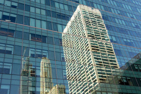 USA, New York, New York City, Skyscraper reflecting in glass wall of building standing opposite - CJMF00196