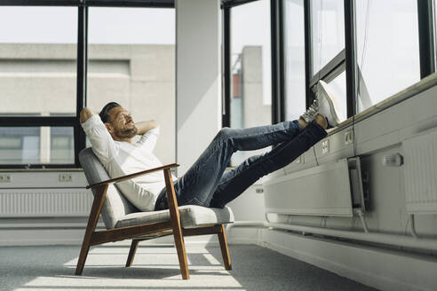 Mature businessman relaxing at the window in empty office - KNSF06879