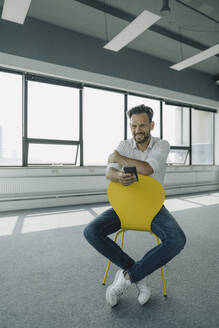 Portrait of confident mature businessman sitting on yellow chair in empty office - KNSF06882