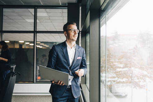 Smiling entrepreneur holding laptop while looking through window in office - MASF15068