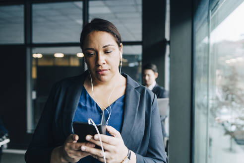 Businesswoman using smart phone while listening through headphones in office - MASF15077