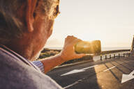 Senior man using smartphone and taking a picture at sunset, Tenerife - SIPF02089