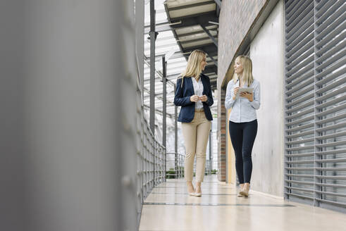 Two young businesswomen with tablet walking and talking in modern office building - JOSF03825