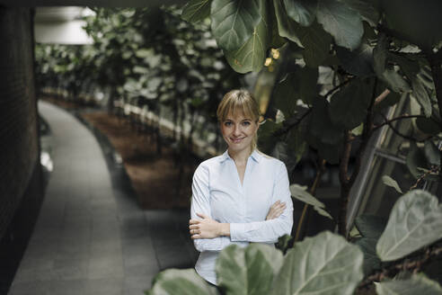 Portrait of a smiling young businesswoman in a modern office building surrounded by plants - JOSF03831