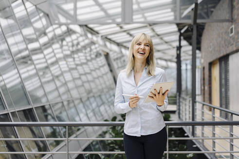 Laughing young businesswoman in a modern office building using tablet - JOSF03840