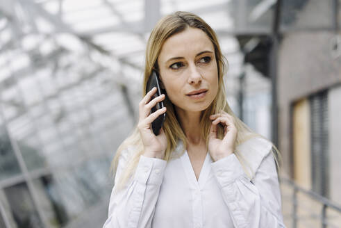 Portrait of a serious young businesswoman on the phone - JOSF03843