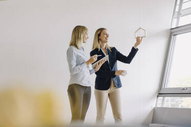 Two young businesswomen with tablet and house model talking in office - JOSF03861