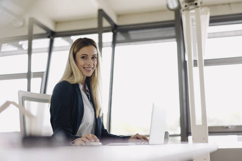 Portrait of a smiling young businesswoman using laptop at desk in office - JOSF03864