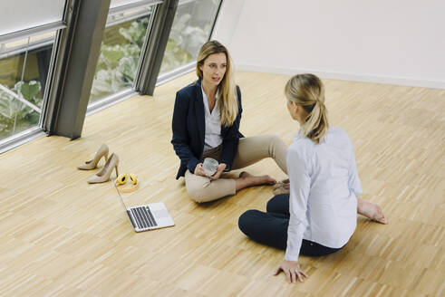 Two young businesswomen sitting on the floor and talking in office - JOSF03870