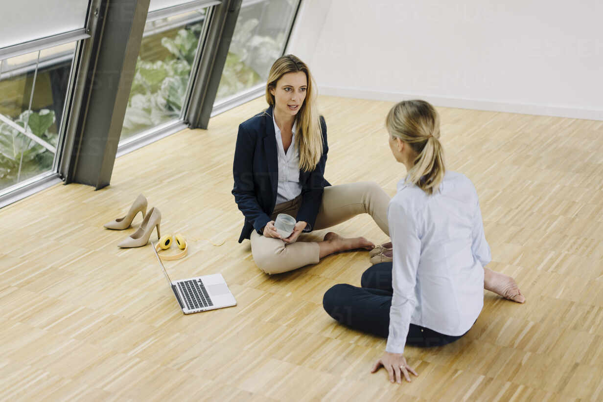 Two young businesswomen sitting on the floor and talking in office - JOSF03870 - Joseffson/Westend61