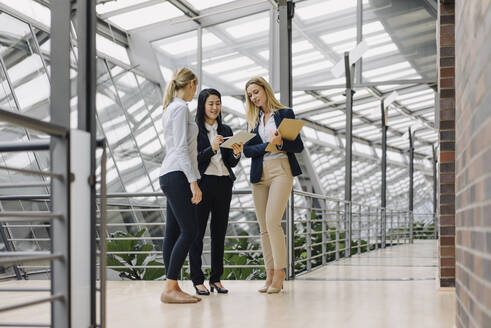 Three businesswomen with tablet talking in modern office building - JOSF03876