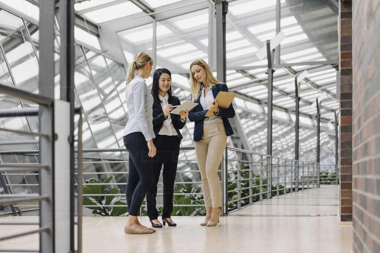 Three businesswomen with tablet talking in modern office building - JOSF03876 - Joseffson/Westend61
