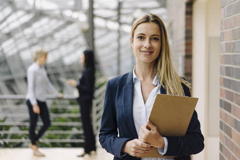 Portrait of a confident young businesswoman in a modern office building with colleagues in background - JOSF03879