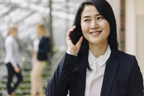 Portrait of a smiling businesswoman on the phone in office with colleagues in background - JOSF03882