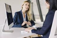 Two businesswomen sitting at desk in office talking - JOSF03885