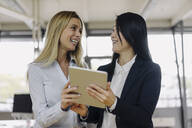 Two happy businesswomen sharing tablet in office - JOSF03891