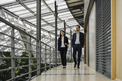 Businessman and businesswoman walking in modern office building - JOSF03900