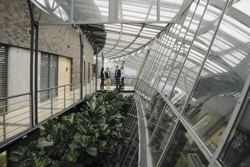 Business people standing on a skywalk in modern office building - JOSF03906