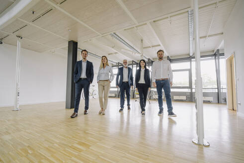 Portrait of confident business people walking in office - JOSF03924
